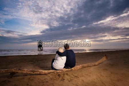 couple watching sunset on beach