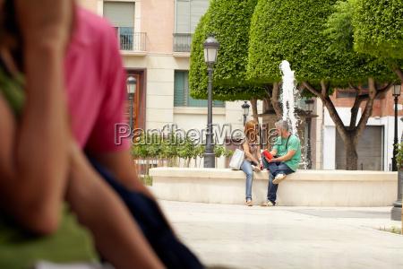 couple sitting next to fountain