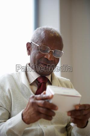 elderly black man reading medicine box