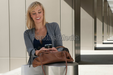 woman reading message on mobile phone