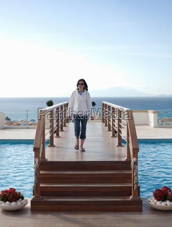 woman on walkway over swimming pool