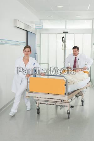 nurse and doctor pushing bed in