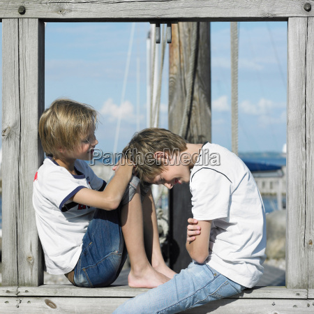 boys sitting on pier