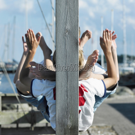 boys sitting together on pier