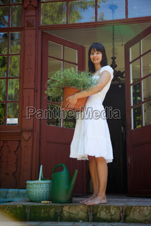 woman carrying potted plant on porch
