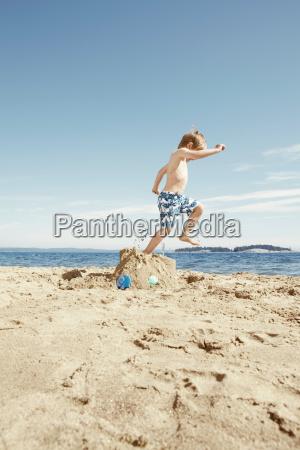 boy stomping on sandcastle on beach