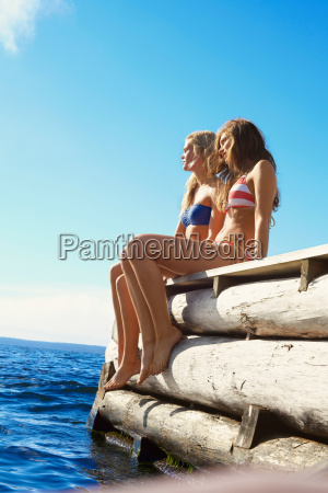 teenage girls dangling legs over pier