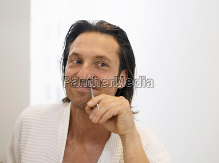 smiling man clipping nose hairs