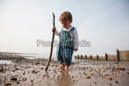 toddler playing with stick on beach
