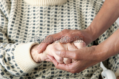 caretaker patting older mans hand