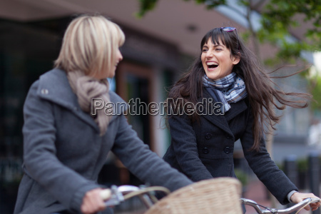 women riding bicycles on city street
