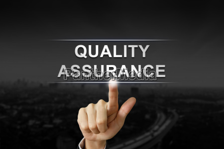 business hand pushing quality assurance button