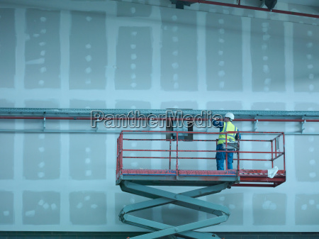 workman on scissor lift of building