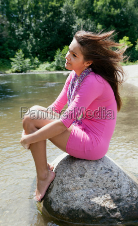 teenage girl sitting on rock in