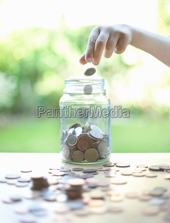 hand tossing coins in change jar