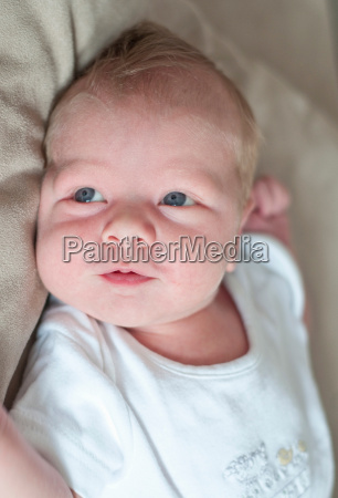 infant boy laying on pillow