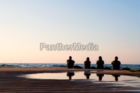 four people sitting on the beach