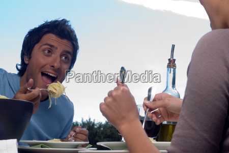 young couple eating pasta