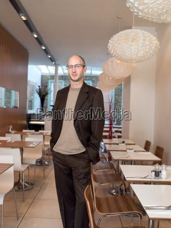 mature man standing in empty restaurant