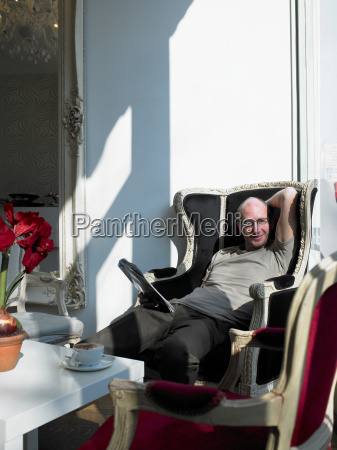 mature man relaxing in armchair in