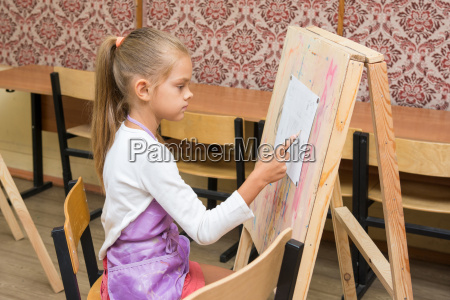 girl artist paints on an easel