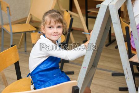 girl draws pencil on an easel