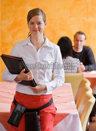 portrait of waiter with menus in