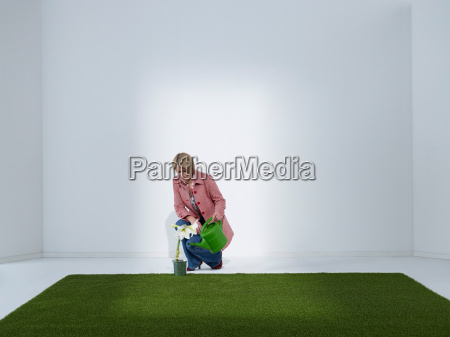 woman watering plant in a green