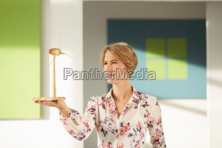 woman looking at wooden wind wheel