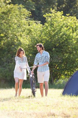 couple walking bike through field