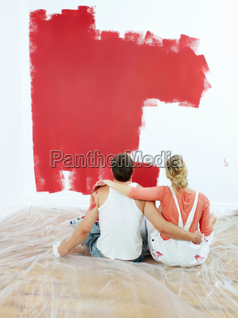 couple contemplating painted wall