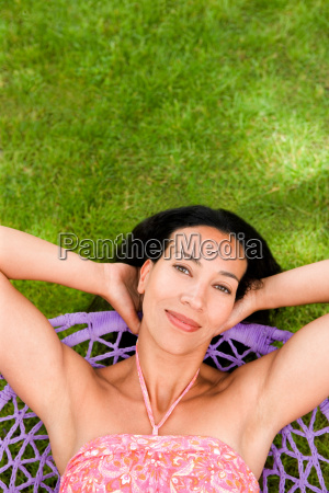 smily woman relaxing in a swing