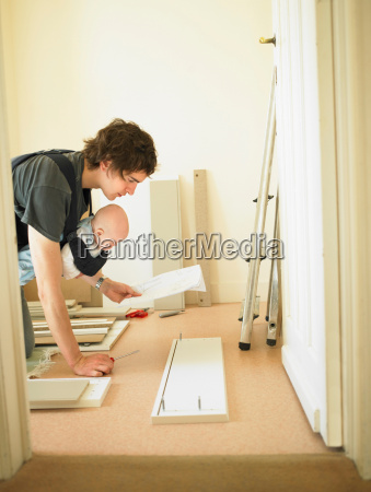 man with baby building furniture