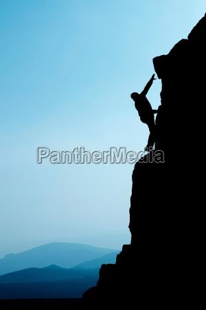 man climbing up rocky hillside