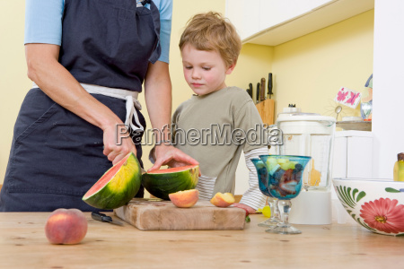 boy and mother preparing fruit