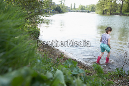 girl in rainboots wading in pond