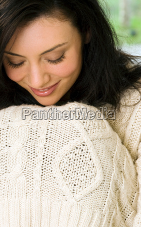 woman pulling sweater over her knees