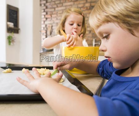 girl boy preparing cookies for baking