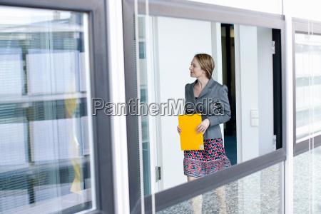 businesswoman carrying folder in office