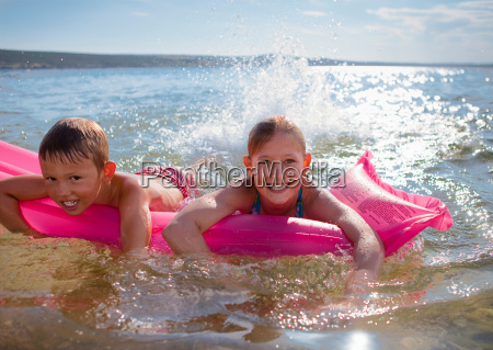 children swimming with inflatable