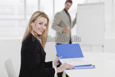 businesswoman reading binder in office