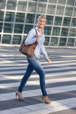 smiling woman crossing city street