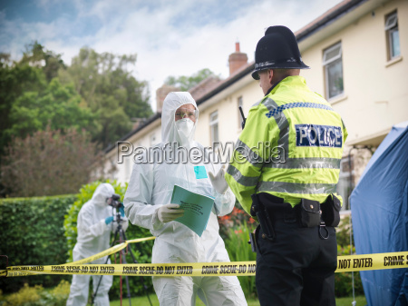 policeman talking to forensic scientists at