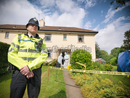 portrait of policeman outside house with