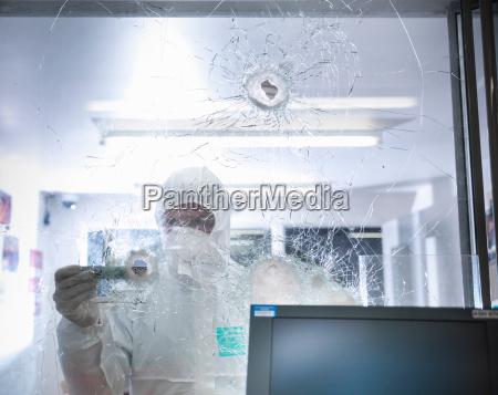forensic scientist measuring bullet hole in