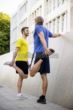 two men stretching hamstrings
