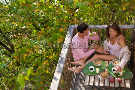 couple eating breakfast outdoors smiling