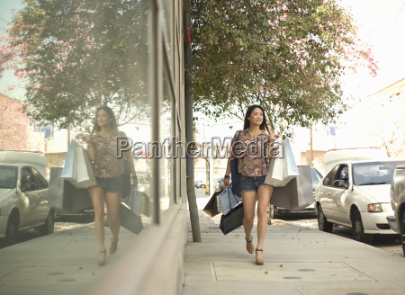 young woman walking down street with