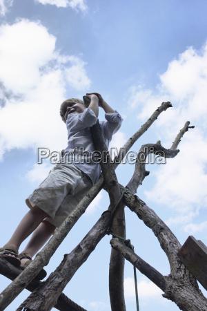 boy climbing branch structure