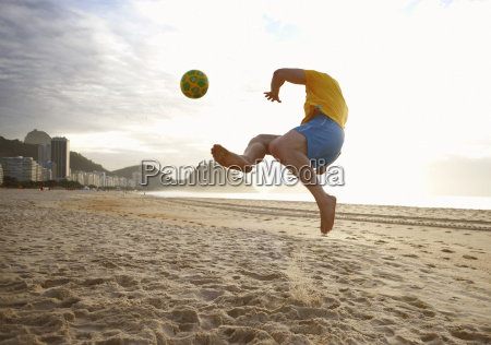 mid adult man playing soccer on